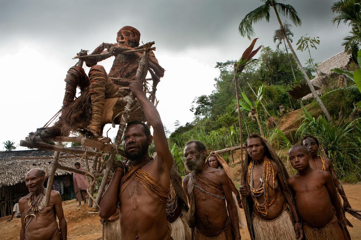 Atalarını köylerinin üst kesimlerindeki mağarasına geri taşıyan bir aile. Papua Yeni Gine'de mumyalanmış aile üyeleri sıklıkla toplum içinde yer alıyor ve köydeki kutlamalara dahil ediliyor. [Fotoğraf: Ulla Lohmann, National Geographic Creative]