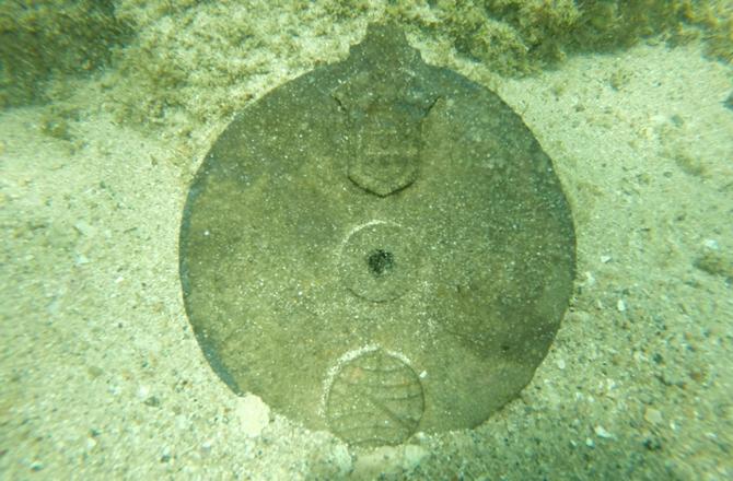Batıkta bulunan Portekiz Kralı 1. Dom Manuel'in kişisel sembolü ile işaretlenmiş bakır alaşımlı disk.